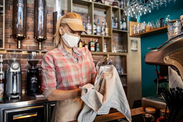 레스토랑에서 바 청소. 웨이터 유니폼을 입은 성인 금발 여성이 바 뒤에 서서 베이지 색 천으로 갓 씻은 와인 잔을 닦습니다. 식당 일과 코로나 바이러스