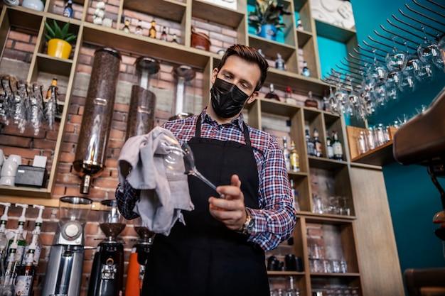 レストランのバーを掃除する。ウェイターの制服を着た大人のハンサムな男がバーの後ろに立ち、洗いたてのワイングラスを布で拭きます。レストランの仕事とコロナウイルス