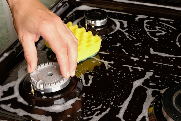 Чистка конфорки на газовой плите, чистка поверхности губкой с моющим средством.
