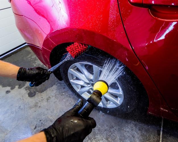 브러시와 물로 자동차 바퀴를 청소하십시오.