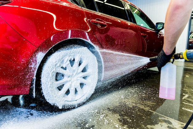 Очистка автомобильного колеса щеткой и водой.