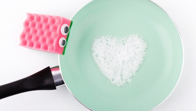 ピンクのスポンジと洗剤で汚れた皿を掃除する