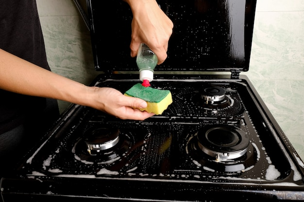 Чистка газовой плиты на кухне моющим средством и губкой. бытовая техника для приготовления пищи. очистка поверхностей.