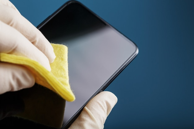 노란색 천과 고무 장갑으로 휴대폰 화면 청소