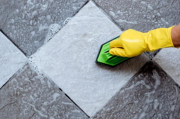 녹색 플라스틱 바닥 수세미로 타일 바닥 청소.