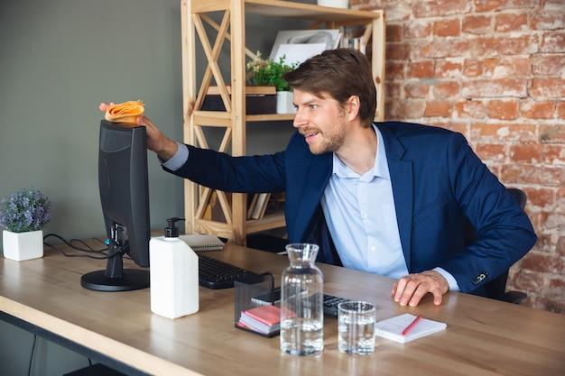 開始前に職場を掃除する。検疫後、マネージャーの若い男性がオフィスに戻り、幸せで刺激を受けました。通常の生活に戻ります。ビジネス、金融、感情の概念。