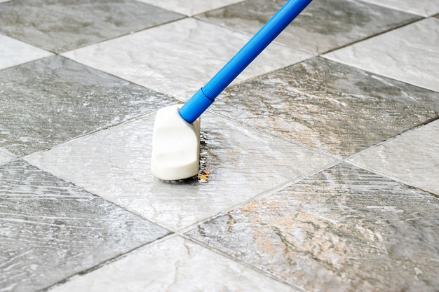 Cleaning the tile floor with a long-handled floor brush
