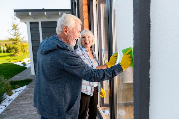 一緒に掃除。一緒に外の窓を洗っている間広く笑っている現代の引退したカップル