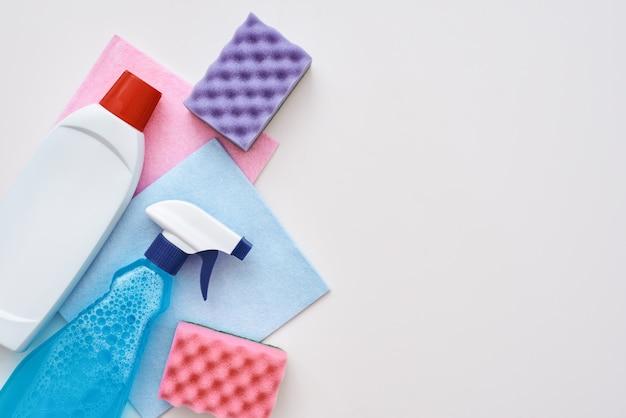 Инструменты для чистки. бутылка с распылителем, фиолетовые губки для очистки и очищающее средство на белом фоне в левом углу изображения