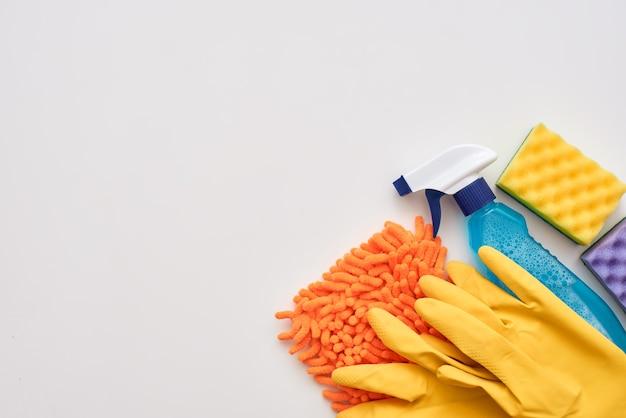 Инструменты для чистки. бутылка с распылителем, фиолетовые губки для очистки и очищающее средство на белом фоне в правом углу изображения