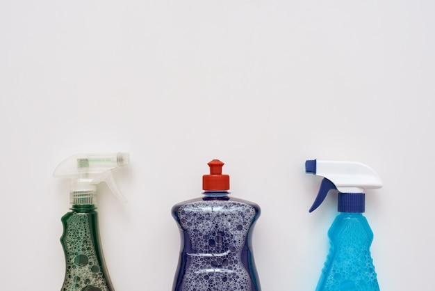 Инструменты для чистки. бутылочки с распылителем и очищающее средство, изолированные внизу изображения