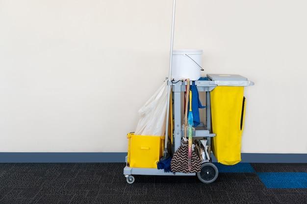 コピースペースのある白い壁面の空港でトロリーまたはハウスキーピングカートを掃除する