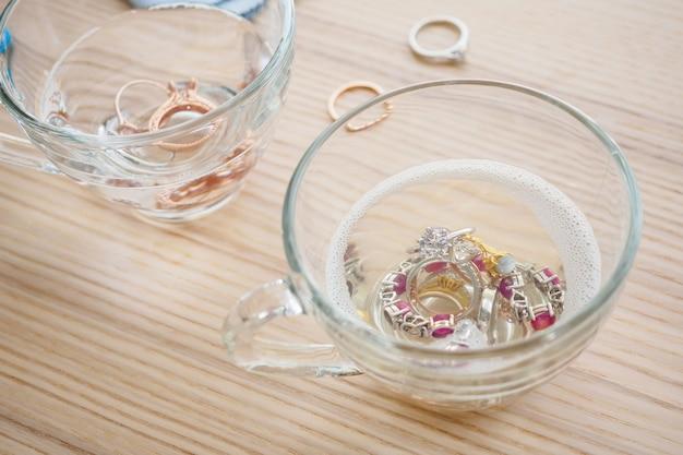 ヴィンテージジュエリーダイヤモンドリングと木製のテーブルの上のガラスのブレスレットのクリーニング