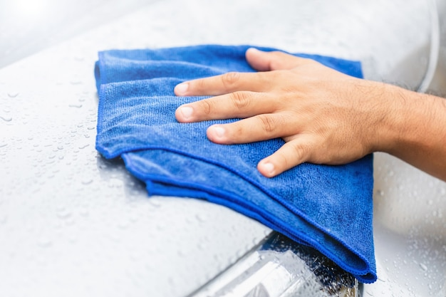 Cleaning or washing car concept : hand holding blue cloth to cleaning wet body of modern car. outdoor shooting in raining day.