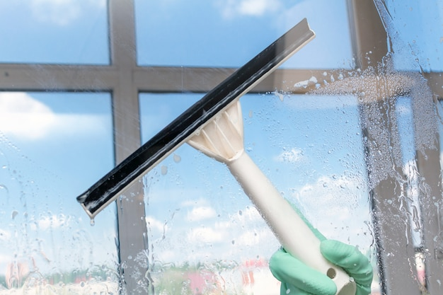 Окно чистки с специальной щеткой на предпосылке голубого неба. сервисное обслуживание.