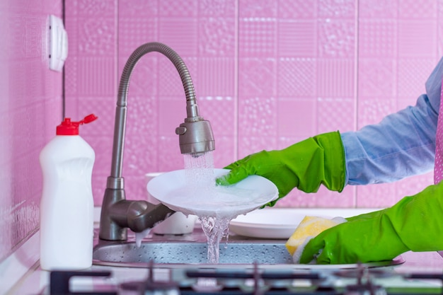 Cleaning woman in green rubber gloves and apron washes dishes at kitchen at home