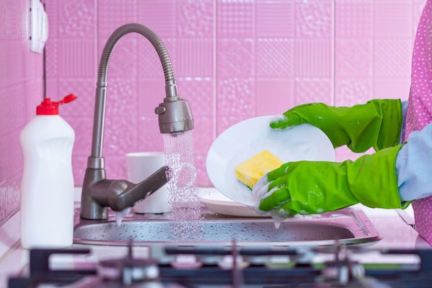 Cleaning woman in green rubber gloves and apron washes dishes with sponge and detergent at kitchen at home