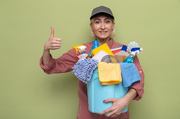 格子縞のシャツと帽子をかぶった女性を掃除する掃除道具を持って笑顔を見せて親指を立てる準備ができている