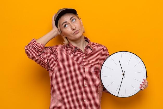 격자 무늬 셔츠와 모자를 쓴 청소 여성이 주황색 배경 위에 어리둥절해 서 있는 시계를 올려다보고 있다