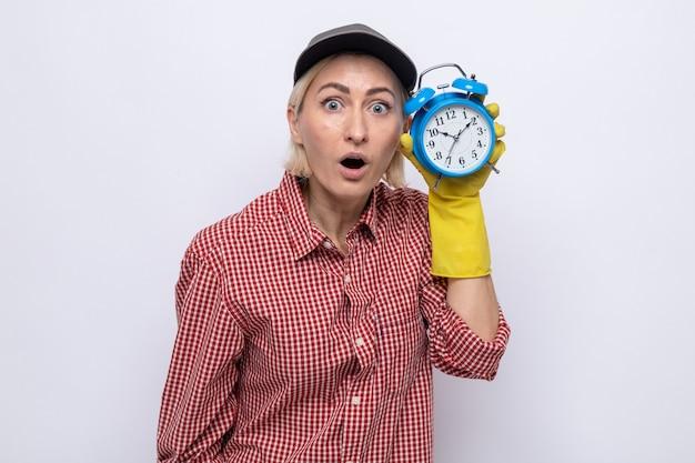 흰색 배경 위에 서 있는 카메라를 보고 놀라고 놀란 시계를 보고 있는 알람을 들고 고무 장갑을 끼고 격자 무늬 셔츠와 모자를 쓴 청소 여성