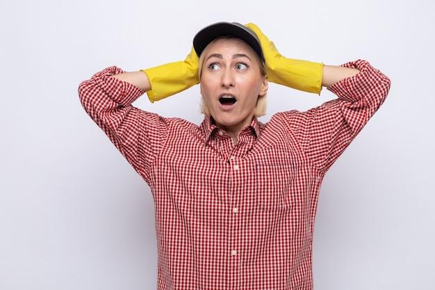 Уборщица в клетчатой рубашке и кепке в резиновых перчатках смотрит в сторону изумленно и удивленно, держась за руки на голове
