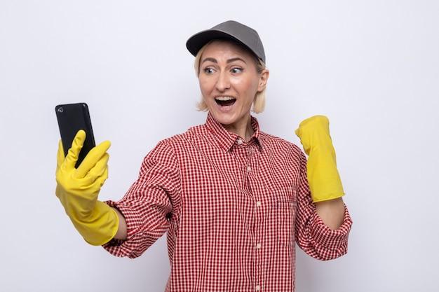 격자 무늬 셔츠와 고무 장갑을 끼고 모자를 쓴 청소부 여성이 휴대폰을 보고 행복하고 흥분한 주먹을 꽉 쥐고 있다