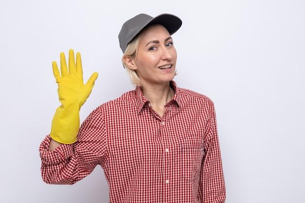 격자 무늬 셔츠와 고무 장갑을 끼고 손을 흔드는 친근한 미소를 짓고 있는 모자를 쓴 청소부