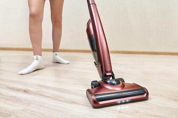 청소 여자는 불이 켜진 휴대용 진공 청소기를 사용하여 빈 방에서 진공 청소기로 청소하고 있습니다.