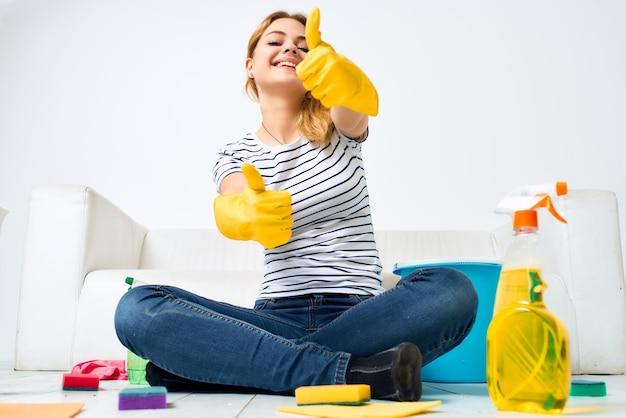 ソファルームの近くで女性を掃除し、保護手袋を掃除します。高品質の写真