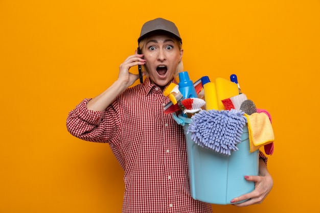 Cleaning woman in plaid shirt and cap holding bucket with cleaning tools looking amazed and surprised while talking on mobile phone