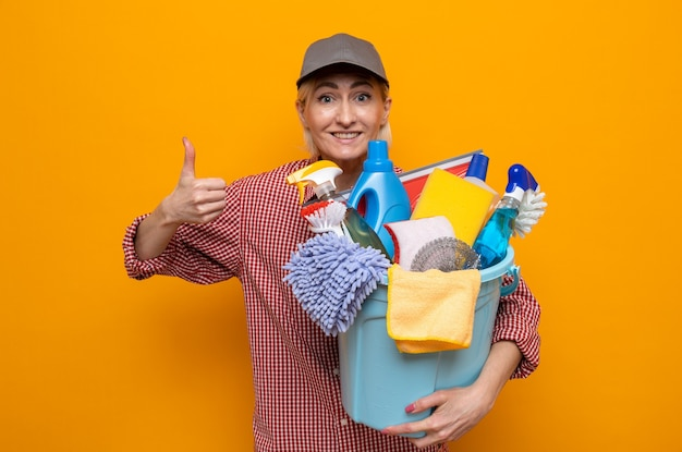 Cleaning woman in plaid shirt and cap holding bucket with cleaning tools looking at camera happy and positive smiling cheerfully showing thumbs up standing over orange background
