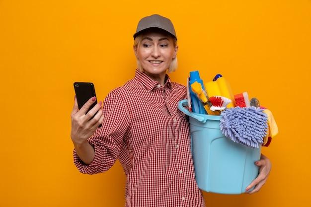 Donna delle pulizie in camicia a quadri e berretto che tiene il secchio con strumenti per la pulizia guardando il suo telefono cellulare con un sorriso sul viso in piedi su sfondo arancione