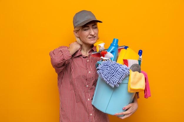 Donna delle pulizie in camicia a quadri e berretto che tiene il secchio con strumenti per la pulizia che sembra indisposto toccandosi il collo sentendo dolore in piedi su sfondo arancione