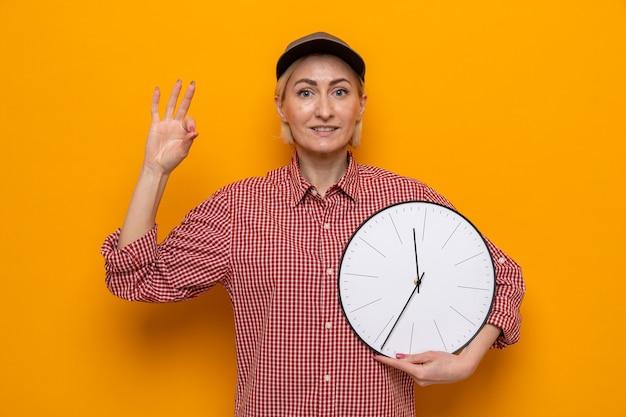 Donna delle pulizie in camicia a quadri e berretto che tiene l'orologio che sembra sorridente fiducioso che mostra segno ok