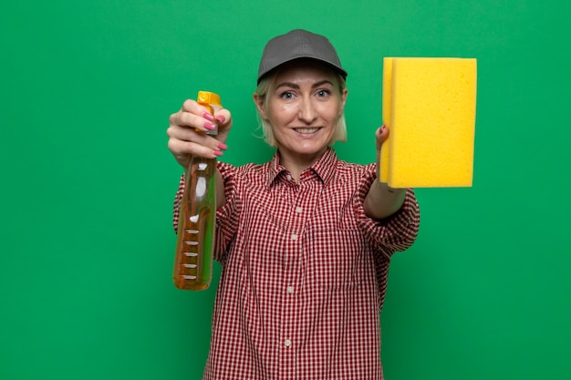 Cleaning woman in plaid shirt and cap holding sponge and cleaning spray looking smiling confident ready fro cleaning