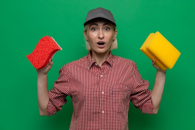 Cleaning woman in plaid shirt and cap holding sponges looking at camera amazed and surprised standing over green background