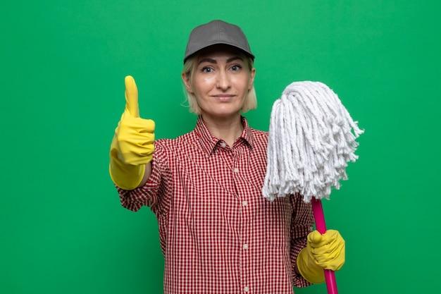 Donna delle pulizie in camicia a quadri e berretto che indossa guanti di gomma che tengono mop guardando la telecamera sorridendo fiducioso che mostra i pollici in su in piedi su sfondo verde