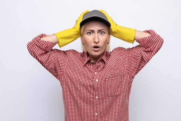 Donna delle pulizie in camicia a quadri e berretto che indossa guanti di gomma che guarda la telecamera stupita e confusa con le mani sulla testa in piedi su sfondo bianco