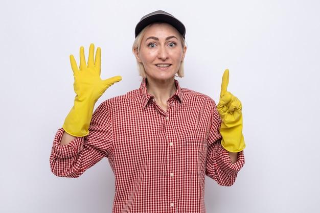 Donna delle pulizie in camicia a quadri e berretto che indossa guanti di gomma guardando la telecamera sorridendo allegramente mostrando il numero sei con le dita in piedi su sfondo bianco