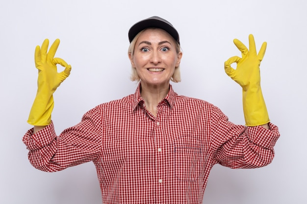 Cleaning woman in plaid shirt and cap wearing rubber gloves looking at camera smiling cheerfully showing ok sign standing over white background
