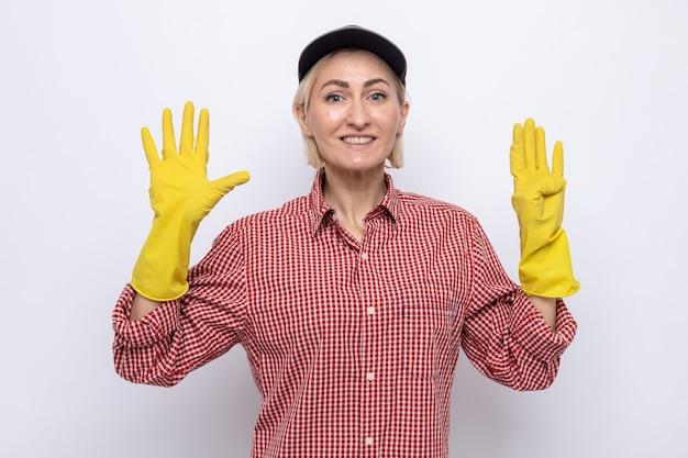 Donna delle pulizie in camicia a quadri e berretto che indossa guanti di gomma che sorride allegramente mostrando il numero nove con le dita