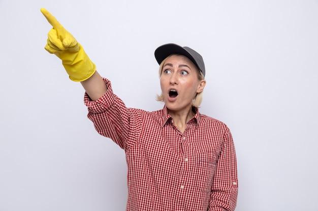 Donna delle pulizie in camicia a quadri e berretto che indossa guanti di gomma che guardano stupiti e sorpresi indicando con il dito indice qualcosa at