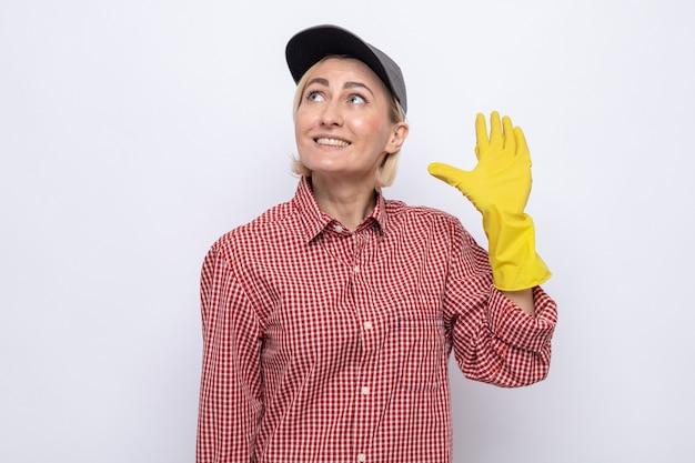 Donna delle pulizie in camicia a quadri e berretto che indossa guanti di gomma alzando lo sguardo sorridendo allegramente salutando con la mano