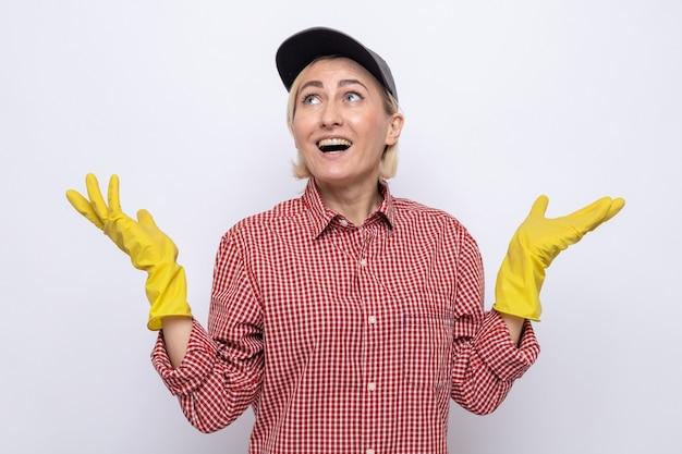 Donna delle pulizie in camicia a quadri e berretto che indossa guanti di gomma che guardano sorridenti allargando le braccia ai lati