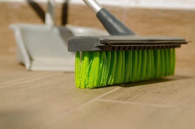 Очистка деревянного пола зеленой пластиковой щеткой щетки, close.housework и ручной sweepi