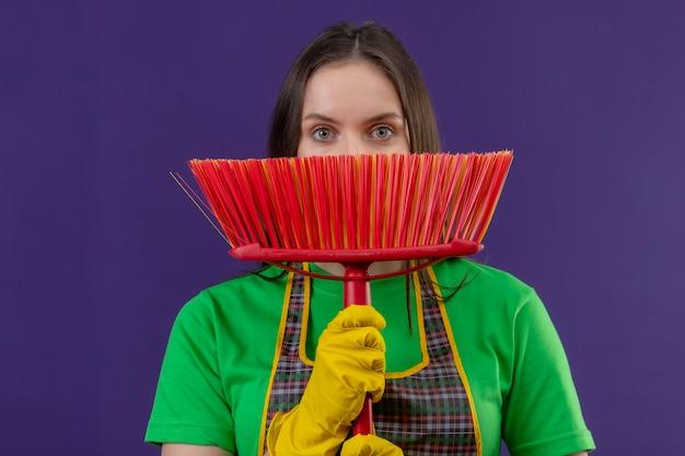 Pulizia giovane donna che indossa l'uniforme in guanti coperto il viso con mop sul muro viola