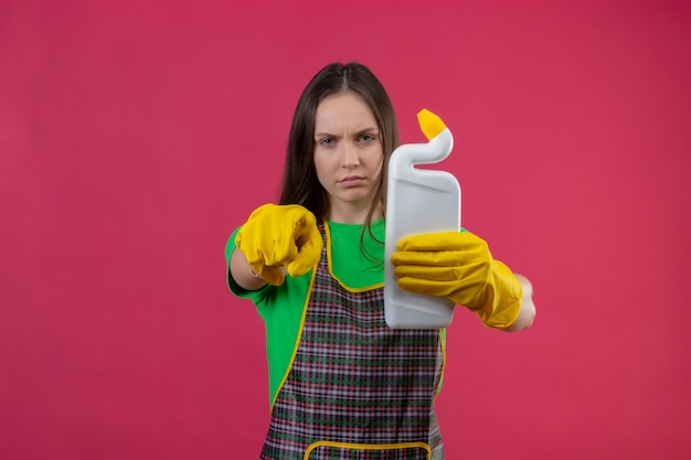 Cleaning young woman wearing uniform in gloves holding cleaning agent showing you gesture on isolated pink wall