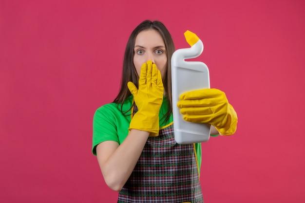 孤立したピンクの壁に手で洗浄剤で覆われた口を保持している手袋で制服を着て若い女性を掃除する