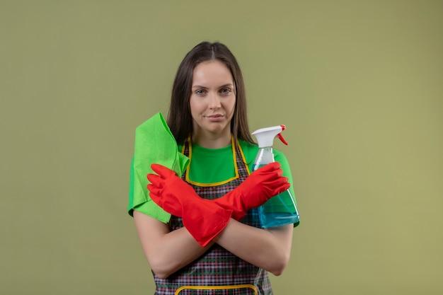 孤立した緑の壁に手を交差するぼろきれでクリーニングスプレーを保持している赤い手袋で制服を着て若い女性を掃除する