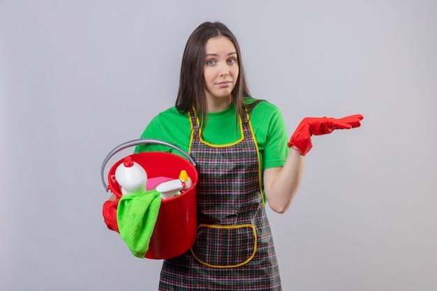 격리 된 흰 벽에 손을 올리는 청소 도구를 들고 빨간 장갑에 유니폼을 입고 젊은 여자를 청소